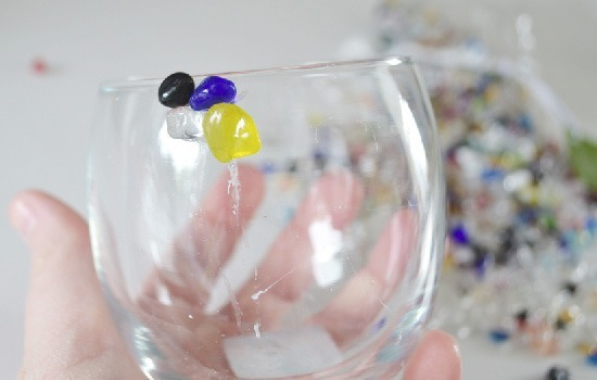Make a pretty candle holder with little pebbles.