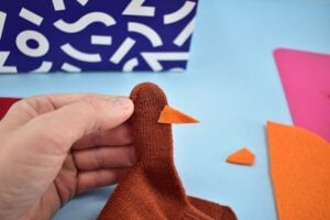 Create the beak for your turkey puppet. Attach the orange triangle onto the thumb of the puppet like you see in the image.