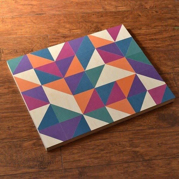 DIY geometric art made with scrapbook paper and a wooden canvas for modern and simple DIY decor.