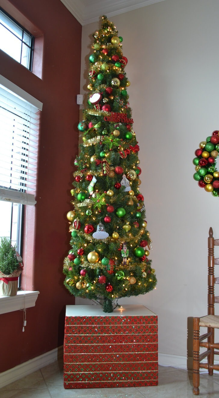 Cover that ugly Christmas tree base with a big gift. This gift just so happens to be very sturdy to keep cats from tipping it over and adds an extra 1.5 feet of height to the tree!