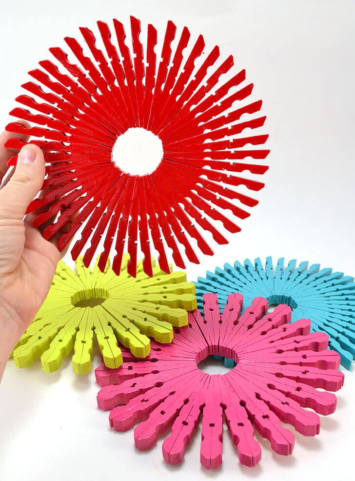 Make colorful and inexpensive trivets out of clothespins! Aren't these wooden clothespin trivets fun?