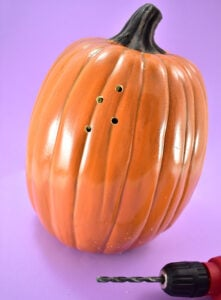 Grab a drill bit that is the size of the holes you'd like in your pumpkin light. Load into the drill and begin randomly drilling holes all around the pumpkin.