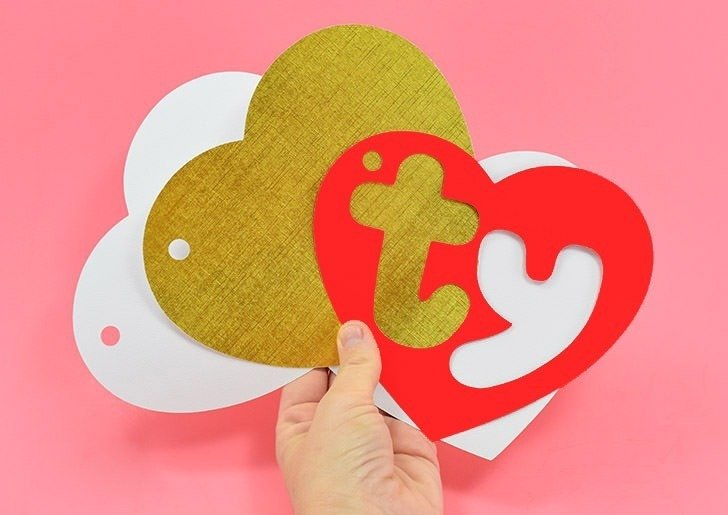 "Using the SVG files, cut out your shapes. You should have 1 large gold heart, 2 white hearts and 1 red heart with ""ty"" cut out."