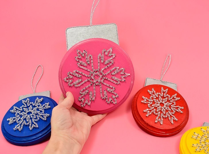 Using wood plaques these awesome string art snowflake ornaments are amazing!