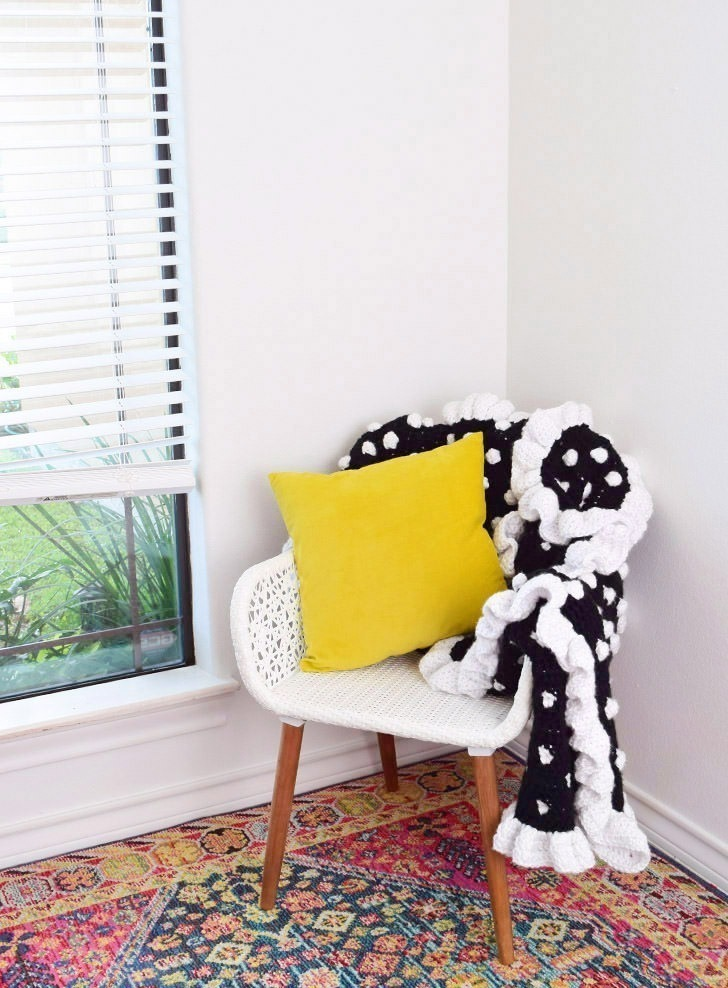 You only need to know basic crochet stitches to hook up this gorgeously girly ruffled edge polka dot crochet afghan that is easy enough for beginners!