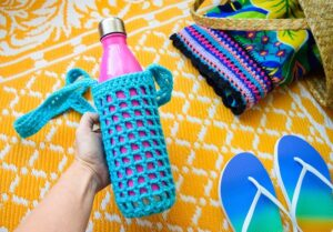Hate holding on to your water bottle? This crochet water bottle holder is a great use of scrap yarn and it keeps your water nearby and your hands free!
