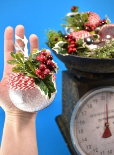 Craft supplies from the bargain bin become simple yet gorgeous baker's twine and holly rustic Christmas ornaments you can make in only 5 minutes apiece!
