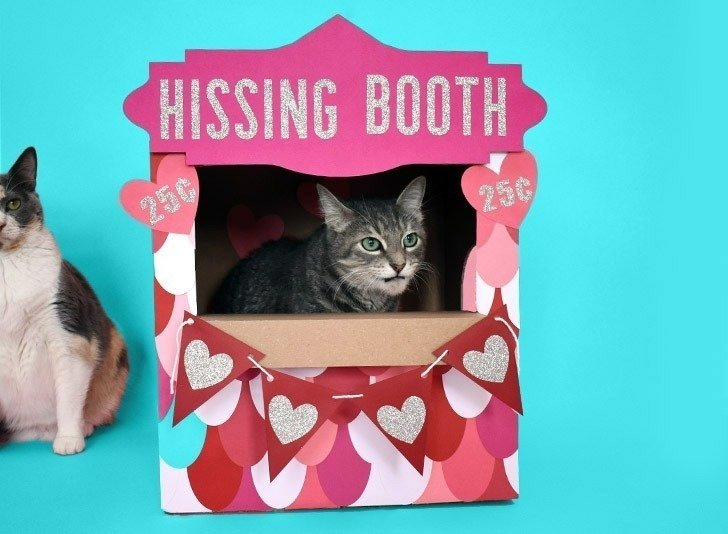 """Don't you just love this """"hissing booth"""" cardboard cat hideaway? All you need is a moving box and some cardstock to make this adorable kitty play place."""