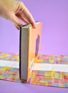 To make your DIY paper book covers, place your textbook in the center of your folded paper, making sure you have the same amount of paper on each side.
