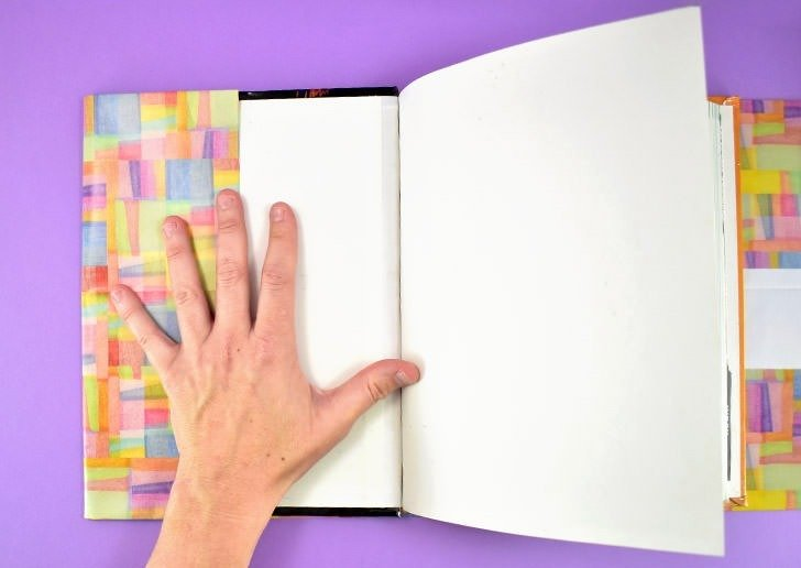 With the book centered, fold the left side over the book's cover, taking care not to include any of the book's pages.
