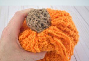 Using orange yarn, stitch the stem in place.