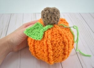 Using the leaf's tail, stitch it into place on the pumpkin's body.