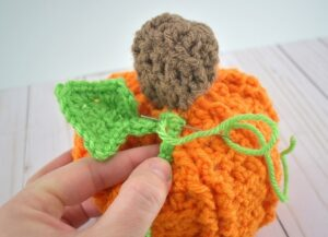 Shove the unfinished end of the pipe cleaner into the pumpkin where you would like it to be placed. Thread the tail through a needle and stitch into place.