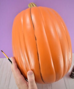 Paint lines of varying thicknesses in the seams of the pumpkin.