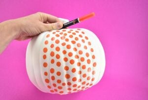 Draw similarly sized dots onto a primed craft pumpkin with a paint pen.