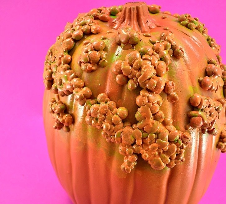 Using burnt umber paint, paint faint lines in the indentations for the pumpkin's segments.