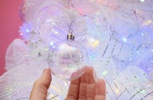 Iridescent clear shatter-proof Christmas ornaments can be placed liberally around the tree. The iridescence helps the colorful Christmas lights inside of the tree bloom and shine.