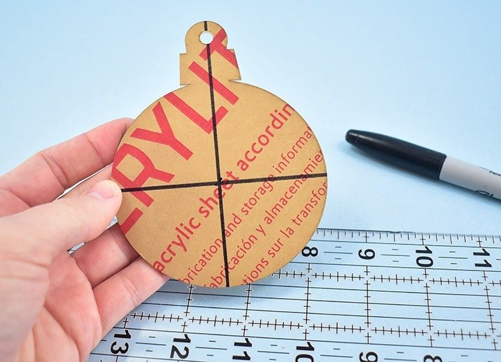 Measure out and draw a cross in the center of the rounded part of your acrylic ornament blank.