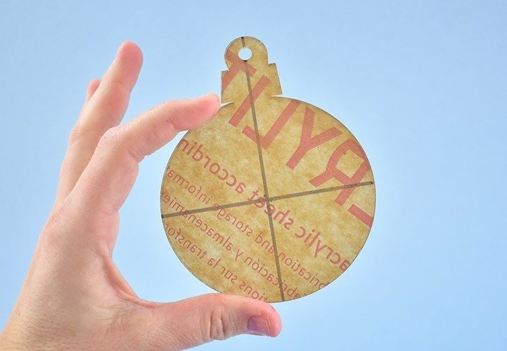 Peel off the protective paper on the other, unmarked side of your acrylic ornament.