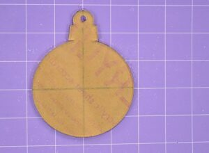Place the paper protected side of the ornament onto the cutting mat directly in the center.