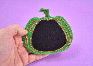 Seat the black felt piece inside of the sewn jack-o-lantern cat toy face.