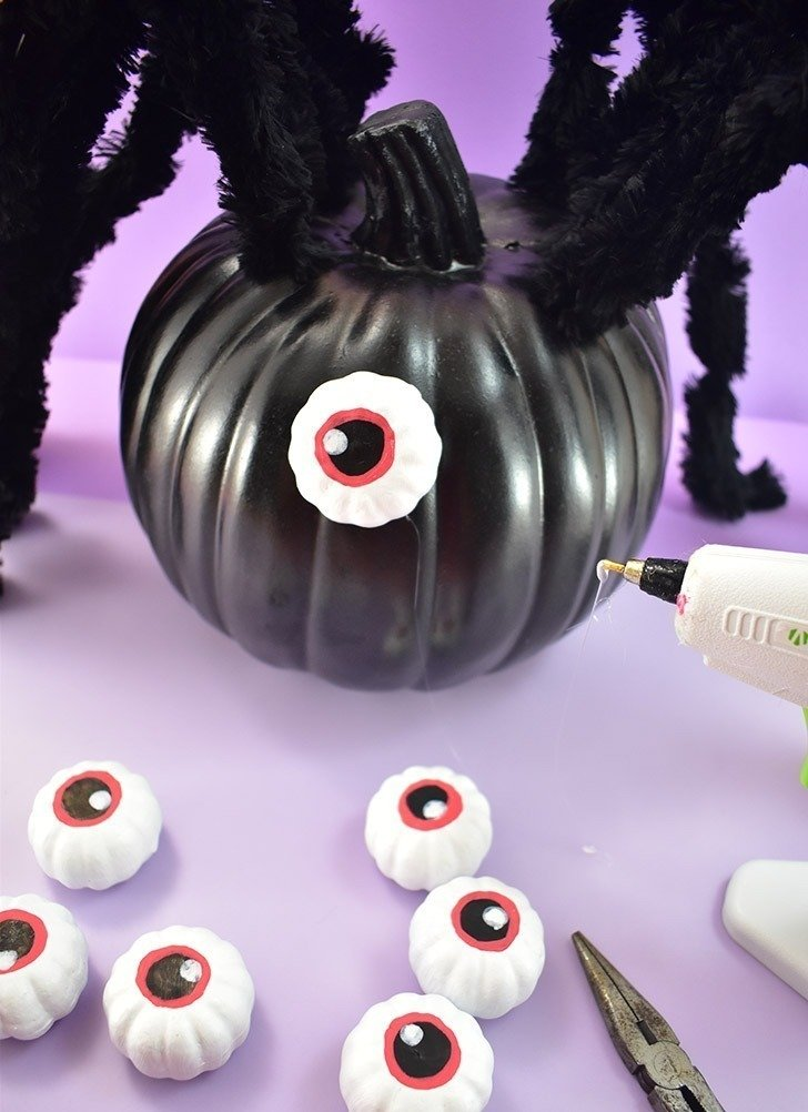 Using hot glue affix your eyes to the front of the pumpkin. Place them nearer the top, practicing before committing with hot glue.