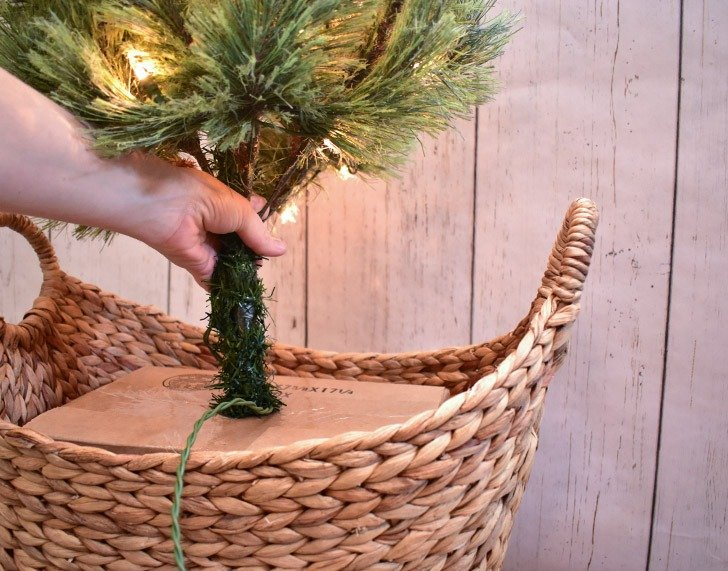 With your cardboard box snugly in place, shove the pole end of the tree into the X cut on the top of the box. You might have to remove the plastic base pieces the tree comes with, but they should easily slide off.
