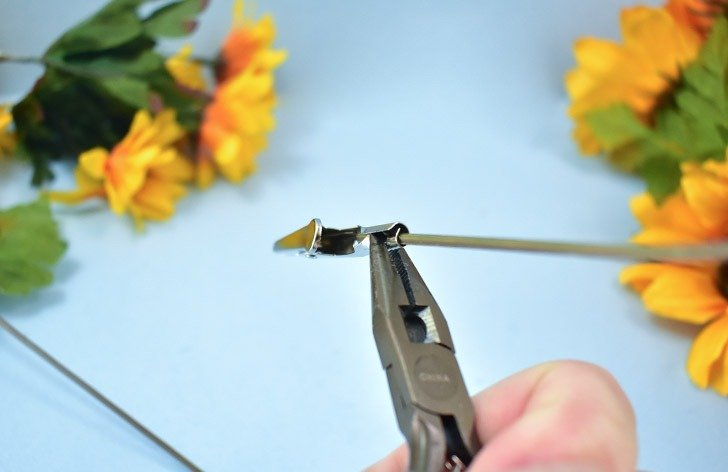 Trim your fake flower to the length you'd like it to be. Run the wire end of it into the tube on the crocodile clamp.
