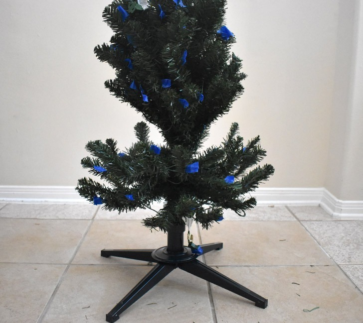 Starting with the first, lowest section of your tree, fluff out the branches and move them where they look best. After flocking it's more difficult to move things around, so be sure you're happy with how the branches look.