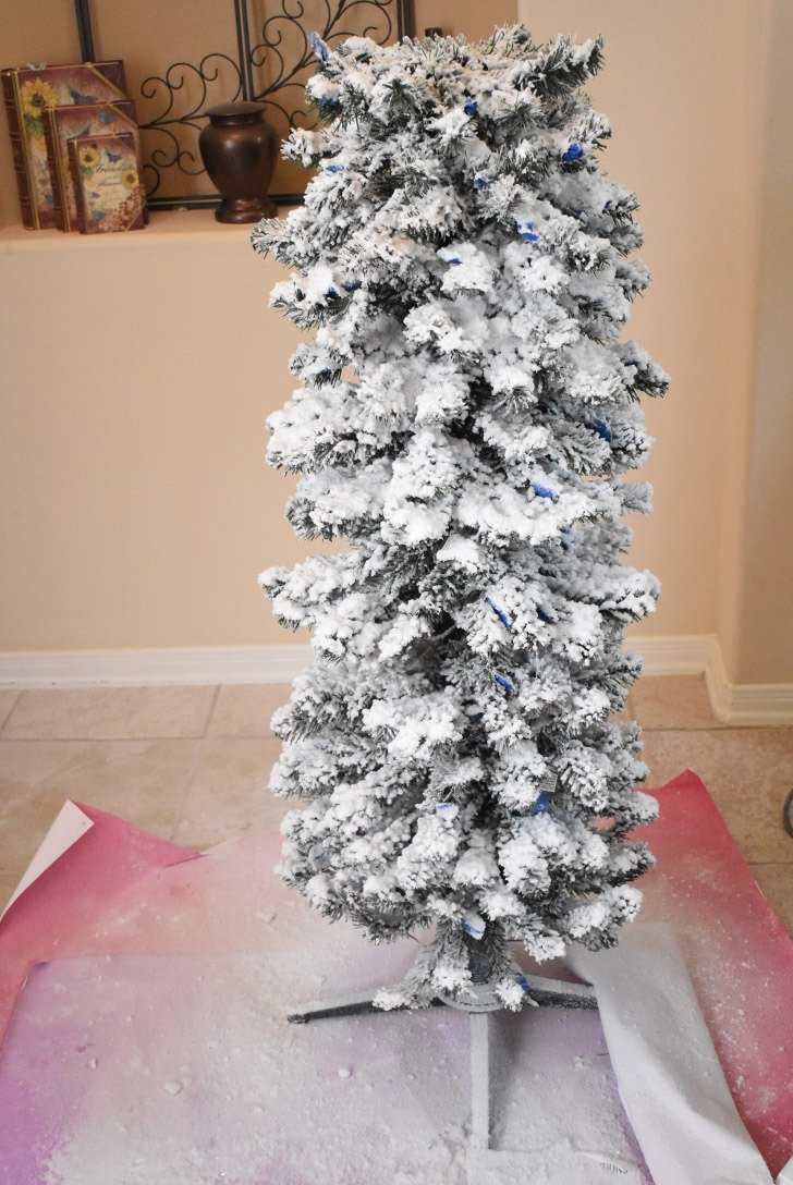 Continue building your tree up, one piece at a time, flocking the individual rounds of branches at a time.