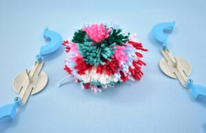 Once well tied, pull the two pieces of the pom pom maker apart like you see above.