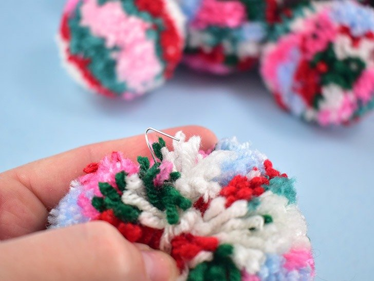 Push the straightened end of the ornament hook through the center of the pom pom. Pinch the end into a sharp hook shape.