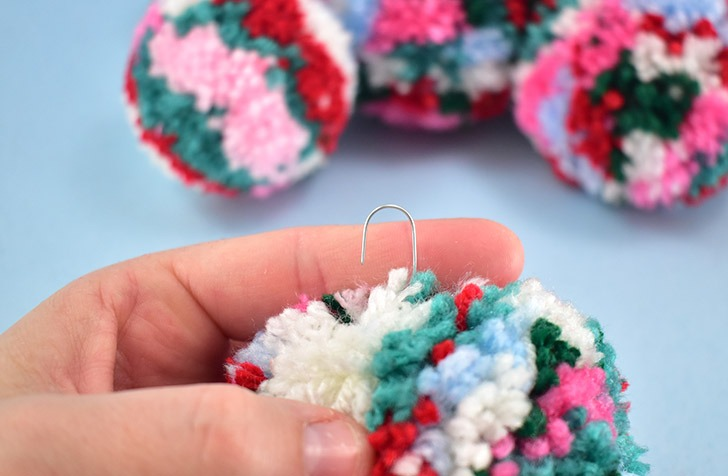 Pull the hook you just made up into the center of the pom pom.