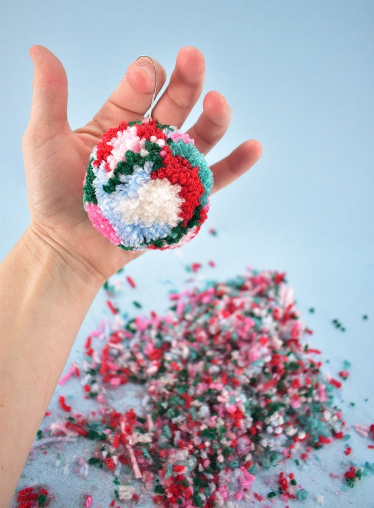 Adding the hook can push some of your yarn bits out of whack. Give each ornament a quick once over with a sharp pair of scissors to neaten up and this craft is done!