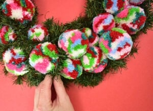 To finish your wreath and to make it look fantastic take the flatened out pine stems and wrap them around your poms.