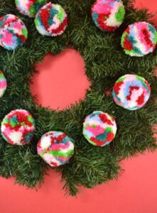 With your flattened out wreath flat on your work surface, place your largest poms where you would like for them to go.