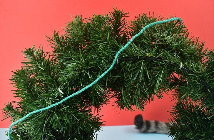 Grab those strings you used to tie your pom pom together to tie each pom onto your wreath in approximately the area you worked out on your work surface.
