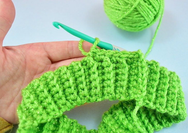 Single crochet around the first stitch from the first row of the ribbing.