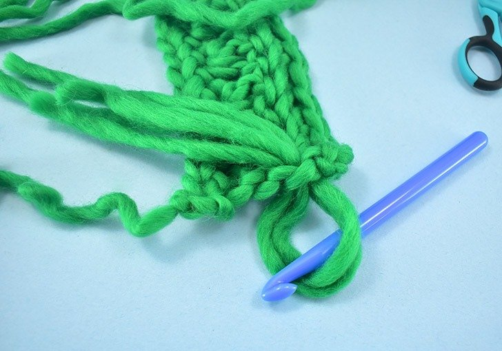Pull the center you found in your yarn pieces through the edge of your scarf.