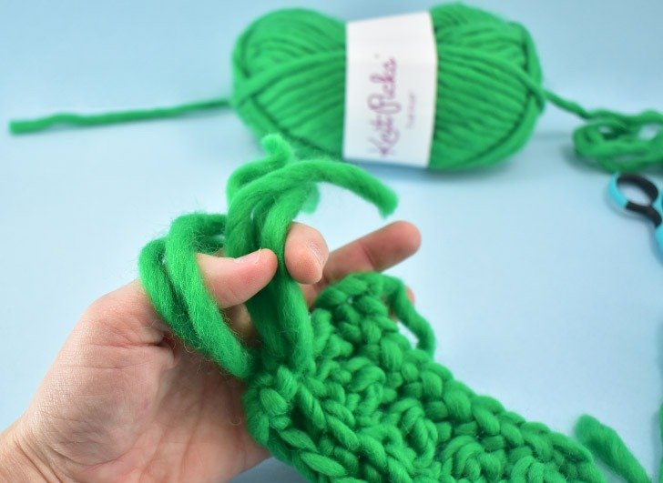 Reach in through the loop and grab the ends of the yarn. Pull through.