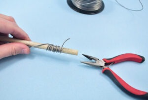 Begin wrapping the wire tightly and neatly along the dowel to create a coil.