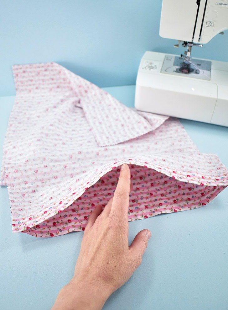 Keeping the piece of fabric folded, you should now have 2 clean sewn edges. To turn this into a pillowcase, we're simply going to sew down the long sides.