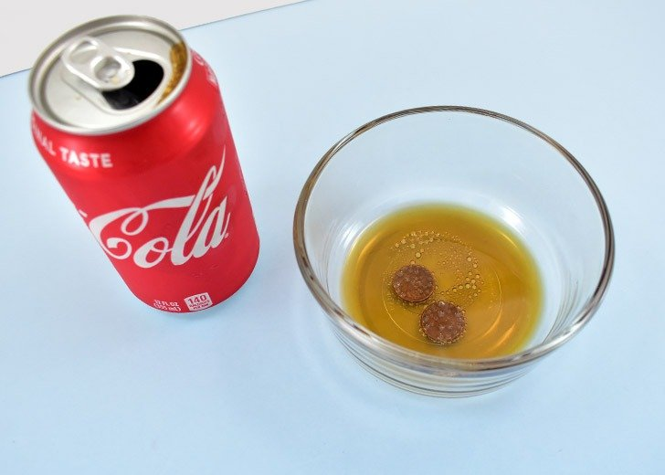 In a small, non-metal bowl, pour cola over your pennies until completely covered.