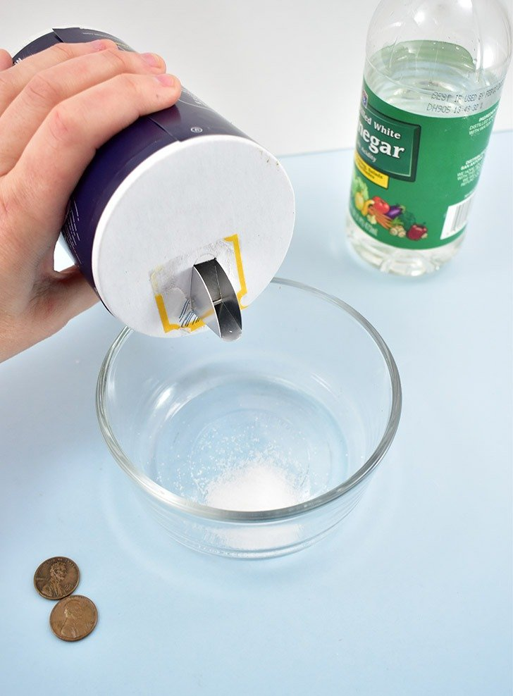In a small non-metal bowl pour 1 teaspoon of table salt and 2 tablespoons of vinegar.