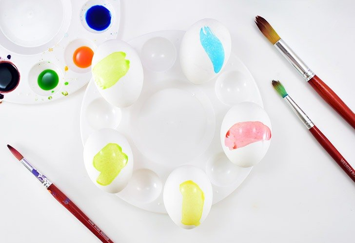 Using a paint palette, egg cups, or something similar place lay out your hard boiled eggs to paint.