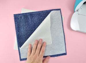 Apply heat using your EasyPress or an Iron onto the paper side of the interfacing to adhere. Work in short bursts of 2 seconds testing the adhesion after the interfacing cools.
