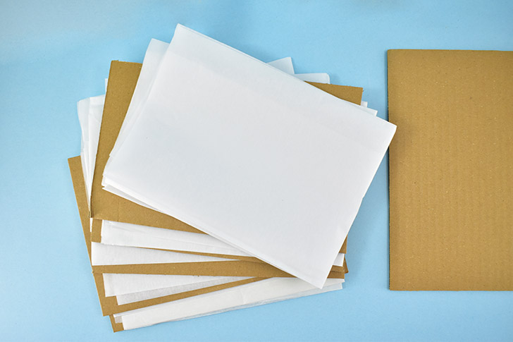 Fold pieces of tissue paper or newspaper to fit within your cardboard pieces, 2 separate sheets to sandwich between each layer of cardboard.