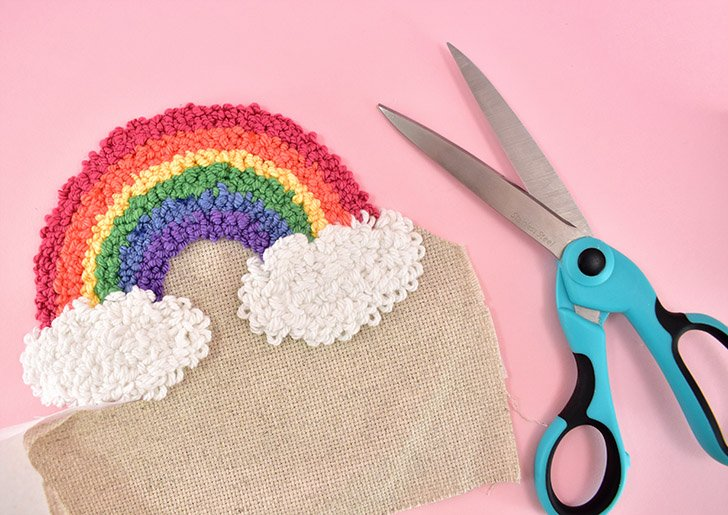 Using sharp scissors, trim the rainbow from the backing material. Leave approximately 0.25 inch all around the design as you trim.