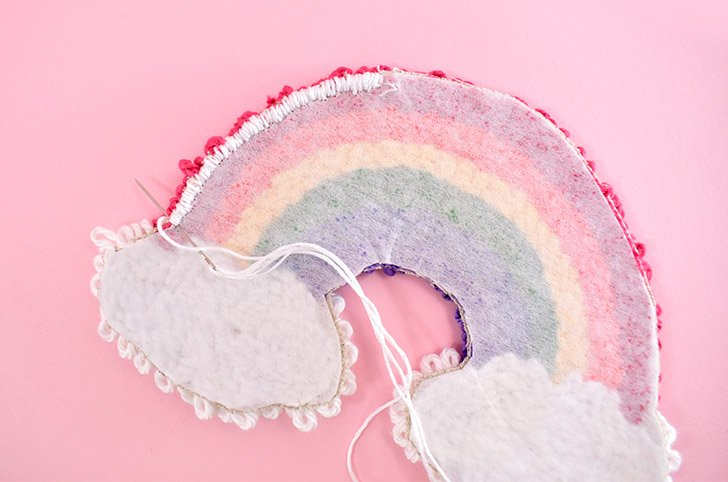 Using a needle and yarn or embroidery floss, whip stitch around the rainbow to hide the raw edge.