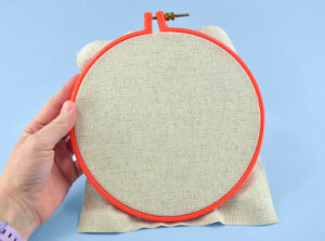 """Place your foundation material in an 8"""" embroidery hoop. Pull the fabric to be as taut as possible within the frame."""